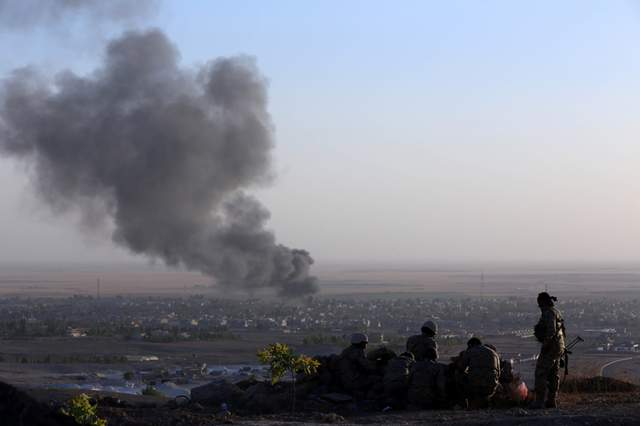 Iraqi Kurdish Peshmerga fighters look on as smoke billows from the town of Makhmur on Aug 9